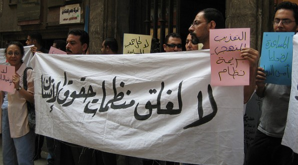 "Activists protest the shut down of AHRLA - Association for Human Rights and Legal Aid. ""No to the closure of human rights organizations,"" says the sign."